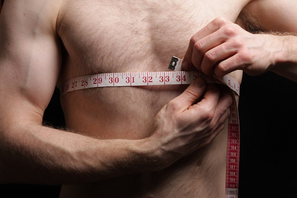 Man measuring his chest size with a measuring tape.