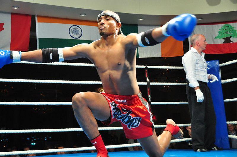 Kickboxer kneeling down in the fighting ring.