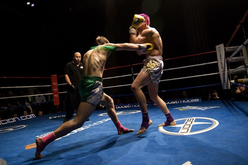 Professional kickboxers fighting in the ring.