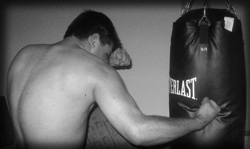 Best punching bag for kickboxing at home: man punching a punching bag