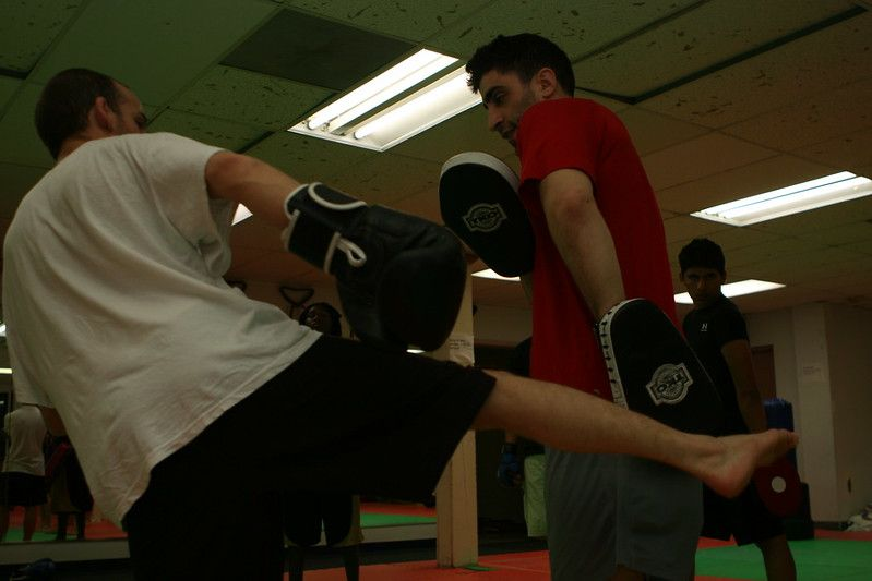 man kicking pads during kickboxing class: who is kickboxing a great alternative for.