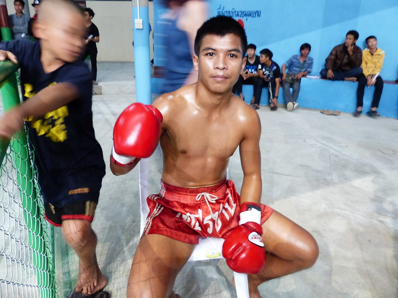 A kid, wearing kickboxing gloves, resting after a kickboxing fight.
