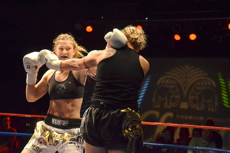 Women kickboxing in the ring to demonstrate how kickboxing is good for self defense.
