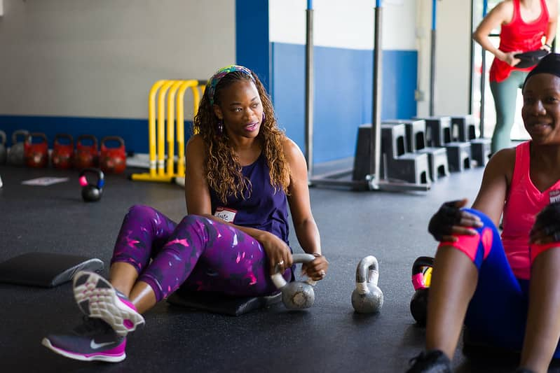 woman sitting on the ground and working out with a kettle bell